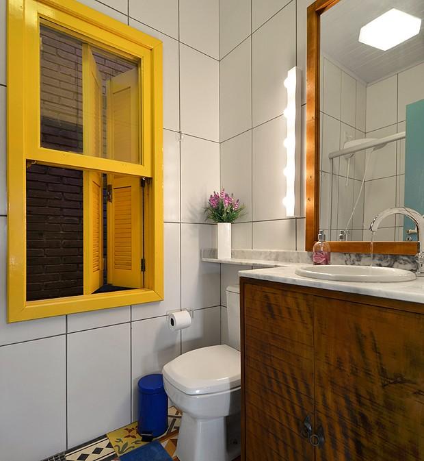 O banheiro da casa tem armário de madeira e piso com ladrilhos coloridos (Foto: Vanessa Bohn/Bohn Fotografias)