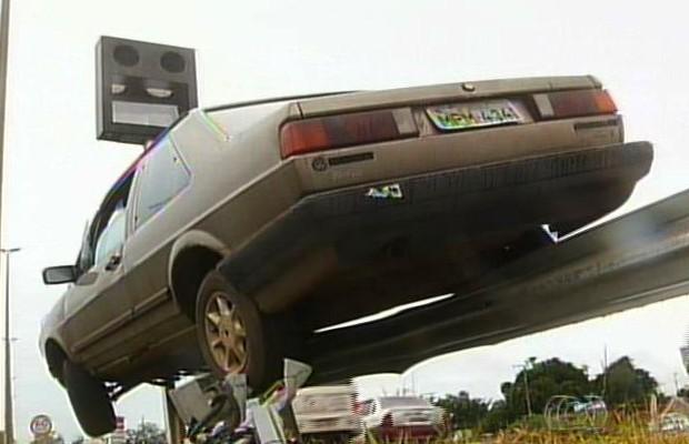 Carro fica pendurado à grade, na BR-040, em Luziânia, Goiás (Foto: Reprodução TV Anhanguera)