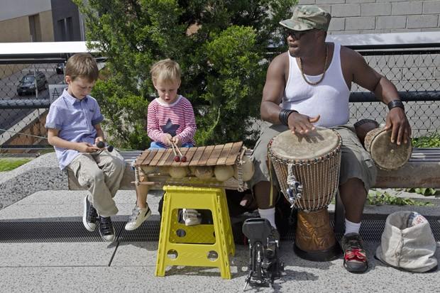 Um músico apresenta-se com seus instrumentos de percussão e convida crianças a participar da festa (Foto:  © Haroldo Castro/Época)