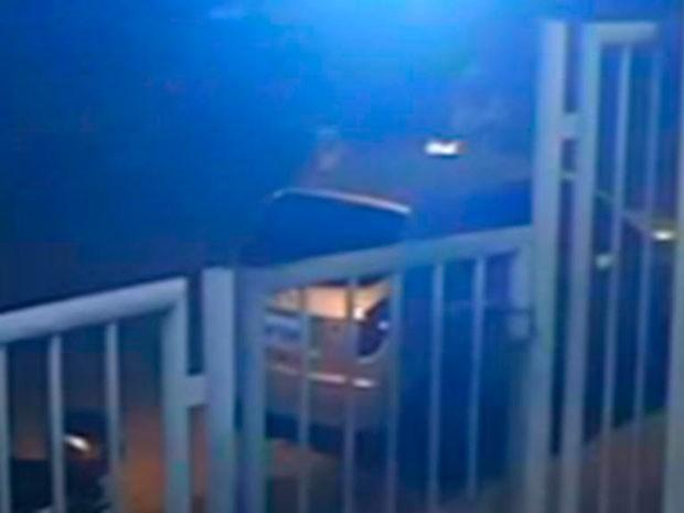 Outro homem vestido com camisa listrada e boné branco virado para traz, se aproxima do estudante e efetua o disparo (Foto: Divulgação / Polícia Civil)