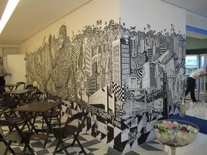 Mural do novo escritório do Google Brasil, em São Paulo, com mesas na frente, feito pelo grafiteiro Rolim  (Foto: Amanda Demetrio/G1)
