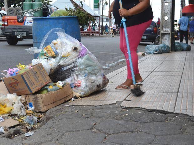Autônoma afasta lixo do ponto de venda de sorvete (Foto: Marina Fontenele/G1)