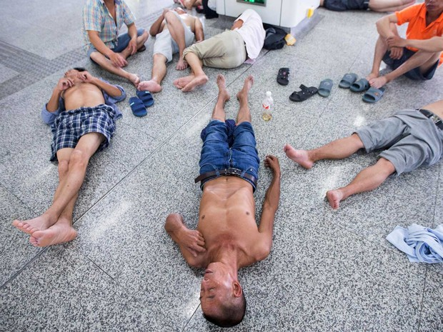 Cineses se resfriam no chão e no ar-condicionado de uma estação de metrô de Hangzhou (Foto: Chinatopix / Via AP Photo)
