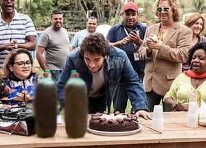 O ator brinca e finge apagar velinhas imaginárias no bolo (Foto: Sangue Bom / TV Globo)