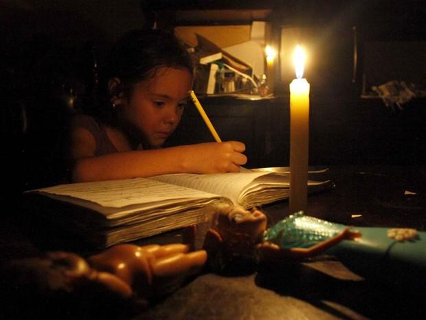 Menina de San Cristobal faz lição de casa com iluminação de uma vela em dia de corte de energia  (Foto: REUTERS/Carlos Eduardo Ramirez)