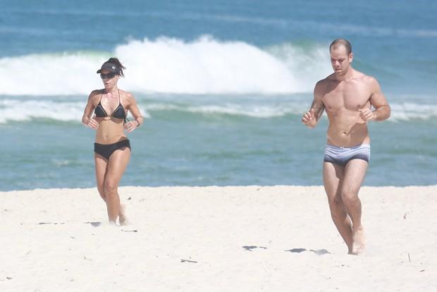 Carla Marins corre com seu marido na praia (Foto: Dilson Silva / Agnews)