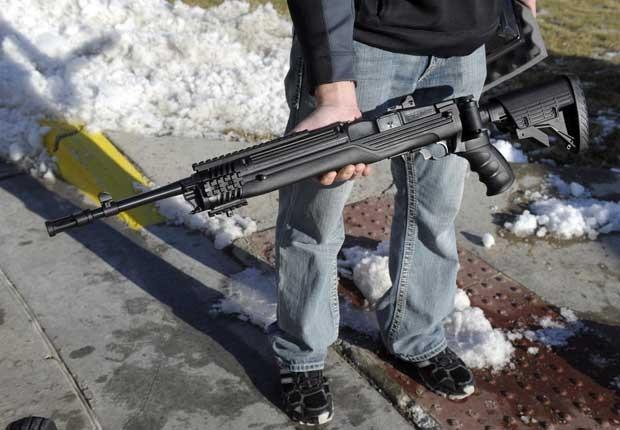 Americano mostra Ruger Mini 14 Rifle que comprou em Kansas City, Missouri, neste sábado (22) (Foto: Reuters)