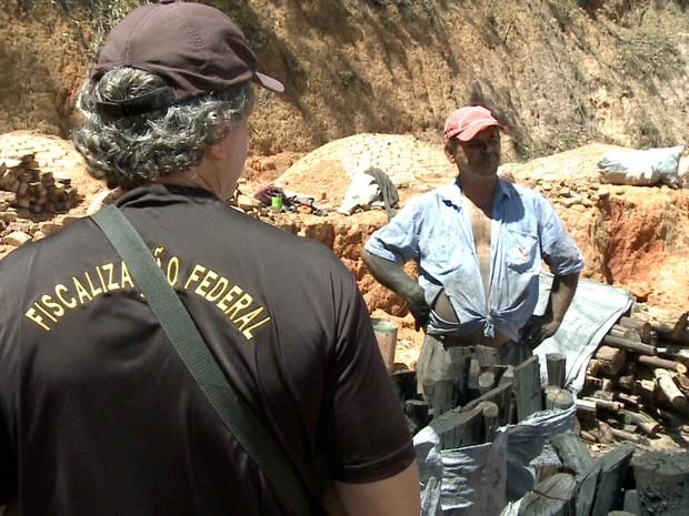 Fiscal conversa com trabalhador encontrado em situação de escravidão em carvoaria de Piracaia (SP). (Foto: Filipe Gonçalves/TV Vanguarda)