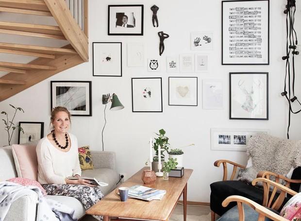 Niki em sua sala com tapete que imita pele e uma manta, itens indispensáveis para quem quer decorar com estilo escandinavo  (Foto: Divulgação)