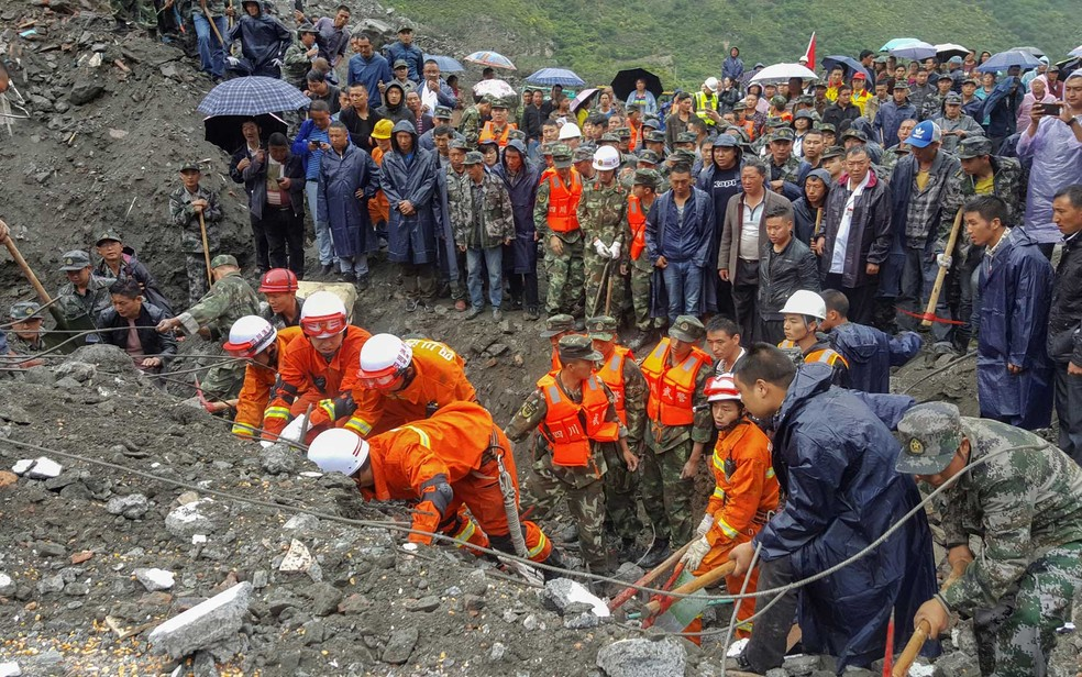Socorristas procuram sobreviventes em área de deslizamento de terra em Xinmo (Foto: China Daily / via Reuters)