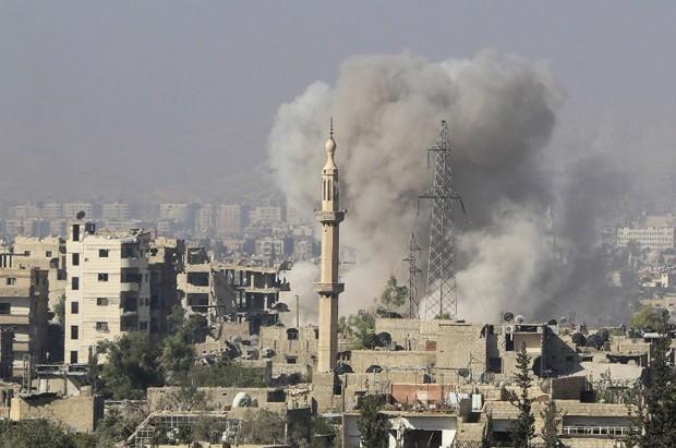 Foto mostra fumaça provocada por explosão em Jobar, a leste de Damasco, na quinta-feira (15). Governo sírio afirmou ter atacado posições rebeldes (Foto: Ammar Suleiman/AFP)
