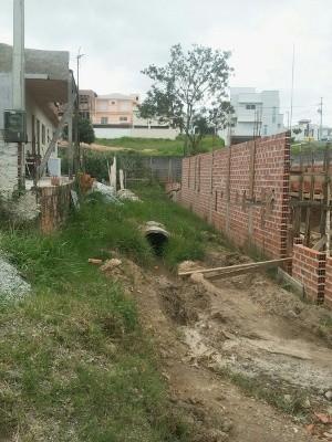 Um duto que escoa água de condomínio próximo à rua piora a situação da cratera (Foto: Geraldo Nascimento Jr. / G1)
