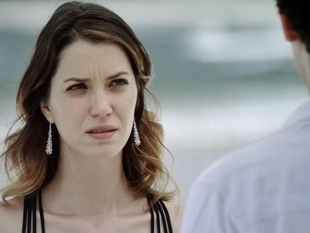 A jornalista estranha quando encontra o médium na praia (Foto: TV Globo)
