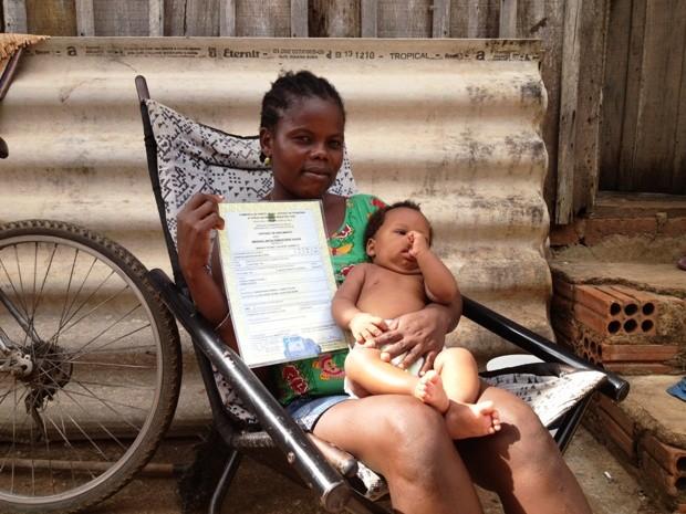 Sunda, que fala somente francês e crioulo, exibe a certidão de nascimento de Emanuel, de 5 meses (Foto: Ivanete Damasceno/G1)