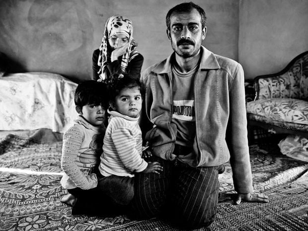 Família síria que teve que fugir devido aos ataques intensos; após deixar tudo para trás, eles vivem em um quarto apertado (Foto: Gabriel Chaim/G1)