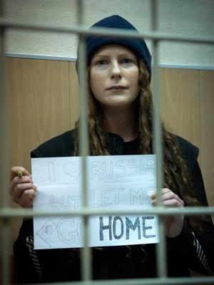 Ana Paula exibe cartaz pedindo para voltar ao Brasil (Foto: Dmitri Sharomov/Greenpeace)