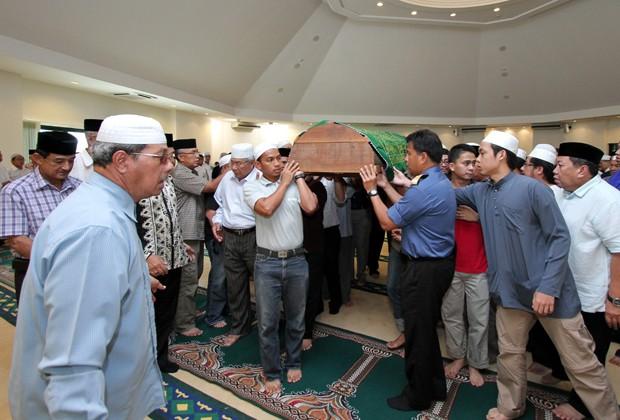 Vítima da queda é carregado por seus familiares neste sábado (21), em Brunei (Foto: AFP PHOTO / DEANKASSIM)