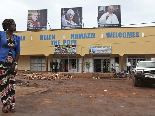 Passageira aguarda táxi perto de retratos que que dão as boas-vindas ao Papa Francisco e lembram as visitas de Paulo VI e João Paulo II, em Kampala, Uganda, no domingo (22) (Foto: AP Photo/Stephen Wandera)