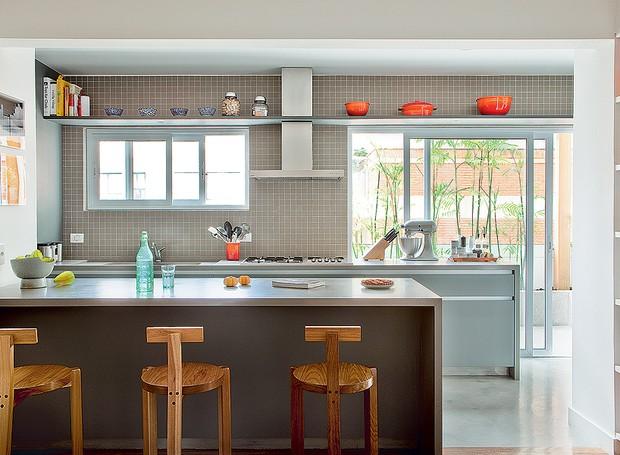 A cozinha do projeto da SAO Arquitetura é cinza, mas ganha graça com as panelas coloridas e as banquetas Girafa (Foto: Edu Castello/Casa e Jardim)