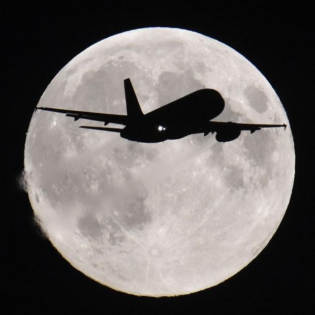 Silhueta de avião pode ser vista passado em frente à Lua em Londres nesta segunda-feira (8) (Foto: Toby Melville/Reuters)