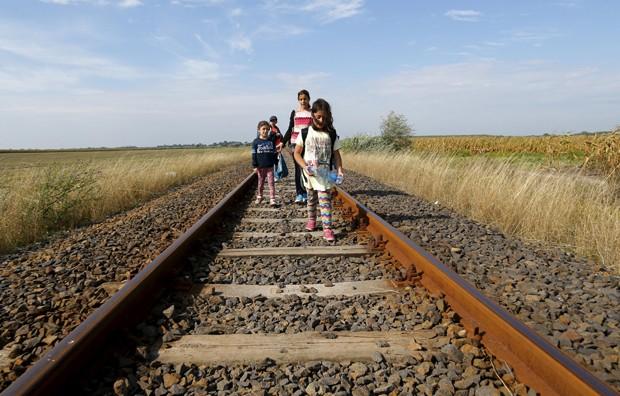 Migrantes sírios atravessam linha de trem na fronteira entre Hungria e Sérvia, próximo de Roszke (Hungria) (Foto: Laszlo Balogh/ Reuters)