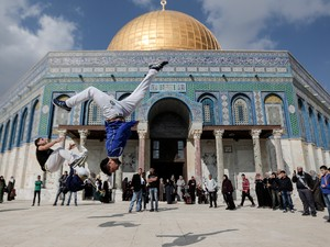 Jovens palestinos praticam parkour em frente à cúpula da mesquita Domo da Rocha na Cidade Velha de Jerusalém. Apesar da onda de violência Israel manteve pela segunda semana o fim da restrição de idade no acesso à esplanada das mesquitas