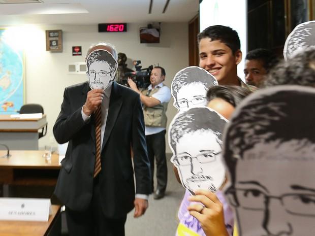 O senador Eduardo Suplicy segura uma máscara do ex-técnico da CIA, Edward Snowden, durante audiência do jornalista Glenn Greenwald, do The Guardian, na Comissão de Relações Exteriores (CRE) do Senado Federal, em Brasília. (Foto: Sergio Lima/Folhapress)