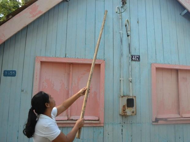 Katicilene Rodrigues mostra onde nível das águas do Rio Acre chegou na casa de Chico Mendes, durante enchente em Xapuri (Foto: Yuri Marcel/G1)