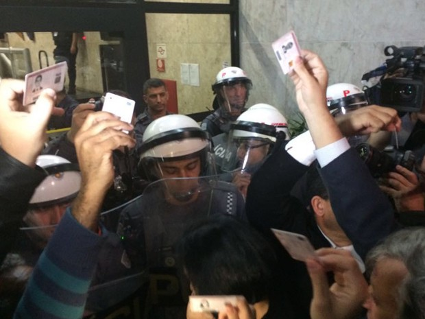 Advogados dos movimentos estudantis tentavam entrar no prédio, mas foram impedidos pelos policiais. Eles mostram o documento da OAB, e ainda assim, são impedidos.. (Foto: Roney Domingos/G1)