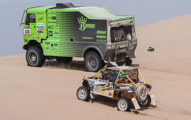 Ao lado de um caminhão, Reinaldo Varela guia sua UTV no Dakar 2013 (Foto: José Mário Dias / Divulgação)
