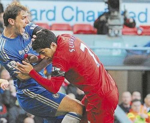 Foto (Foto: Ivanovic tenta se livrar de Suarez após o atacante do Liverpool tentar mordê-lo no braço - Foto: AFP/21-04-2013)