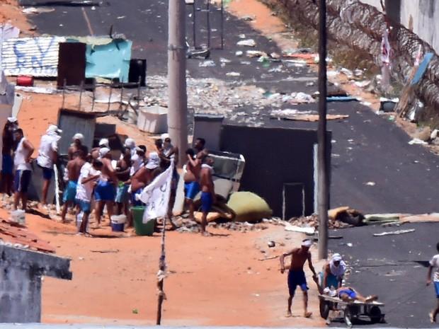 19/01 - Um preso ferido é puxado por outros em um carrinho durante um confronto de facções na penitenciária de Alcaçuz, perto de Natal, no Rio Grande do Norte (Foto: Josemar Gonçalves/Reuters)