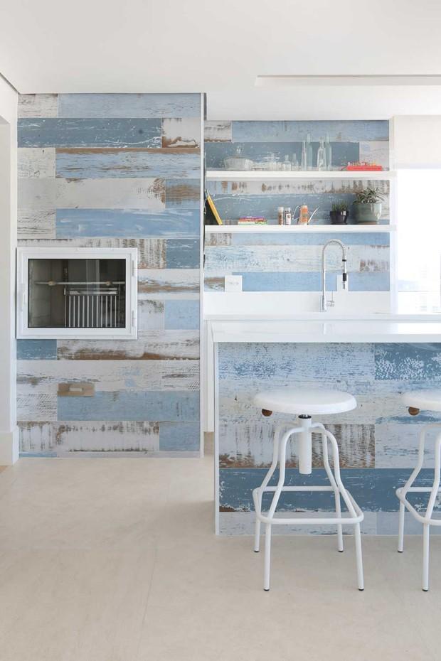 Varanda Gourmet | Integrada ao living, o ambiente tem revestimento da Portinari. Banqueta da Desmobilia. Bancos da XXX  (Foto: Mariana Orsi/Divulgação)