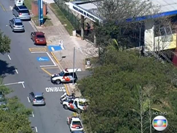 Viaturas da Polícia Militar na porta da Faculdade de Odontologia da USP após assalto em agência bancária (Foto: TV Globo/Reprodução)