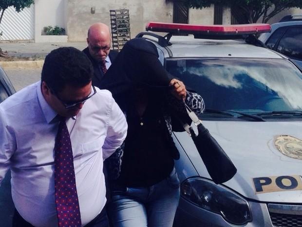 Professora suspeita de dar suco com tranquilizante para crianças chegou coberta com o paletó de um dos advogados para prestar depoimento (Foto: Kamylla Lima/G1)