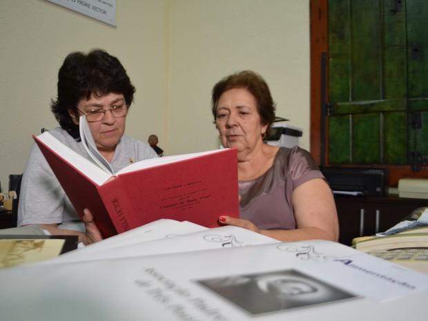 Adriana e Denise seguram o Positio, que contém toda a pesquisa histórica de Padre Victor (Foto: Samantha Silva / G1)