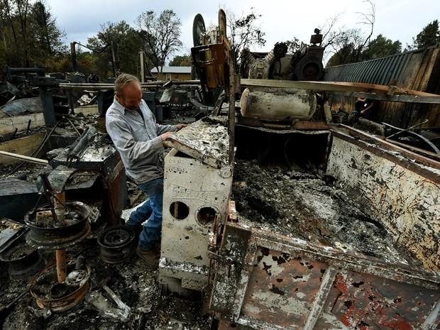 Larry Menzio examina as ruínas de sua loja de automóveis, que foi atingida por um incêndio em Middletown, na Califórnia, na quarta (16) (Foto: AFP Photo/Mark Ralston)