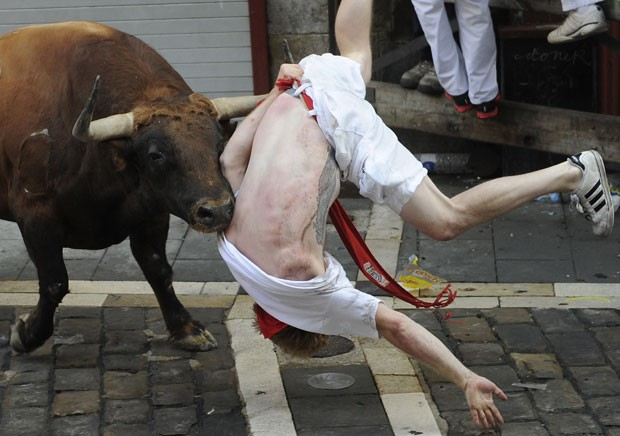 Touro ataca participante na primeira corrida do festival de Pamplona nesta terça-feira (7) (Foto: Ander Gillenea/AFP)