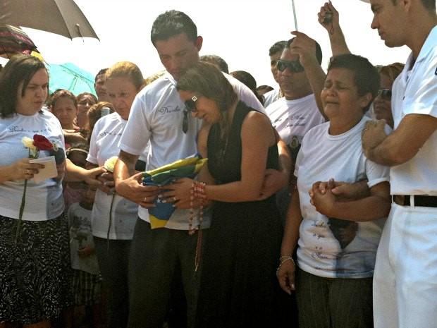 Viúva de Fábio Maciel segura Bandeira Nacional durante enterro (Foto: Camila Henriques/G1 AM)