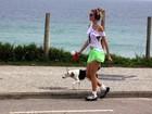 De shortinho, Ellen Jabour passeia com cachorro na praia
