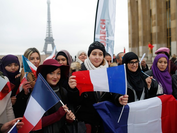 Mulheres seguram bandeiras da França em manifestação neste domingo (13), um mês após ataques  (Foto: Reuters/Stephane Mahe)