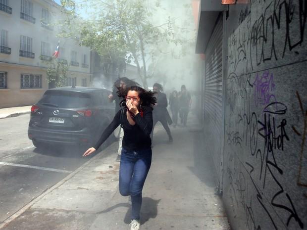 Mulher corre para fugir de bombas de de gás lacrimogêneo jogadas pela polícia após marcha estudantil em Santiago, no Chile. A manifestação cobrava os atrasos na reforma da educação e a promessa da presidente Michelle Bachelet de educação gratuita (Foto: Luis Hidalgo/AP)