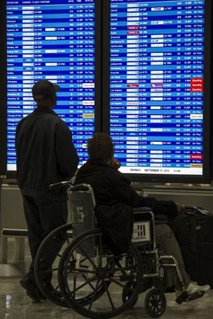 Mulher de cadeira de rodas no aeroporto; companhias aéreas não poderão cobrar para transportar o equipamento (Foto: Paul J. Richards/AFP)