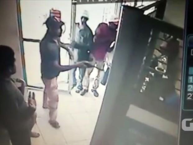 Logo que cruzam a porta, assaltantes sacam as armas e anunciam o assalto (Foto: PM/Divulgação)