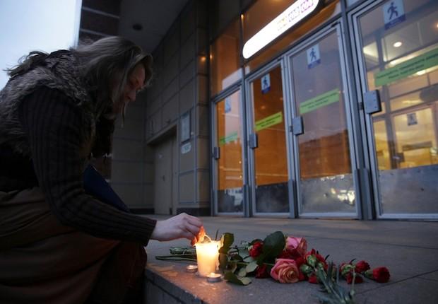 Mulher acende velas para vítimas da explosão que deixou mortos e feridos no metrô de São Petersburgo, na Rússia (Foto: Anton Vaganov/Reuters)
