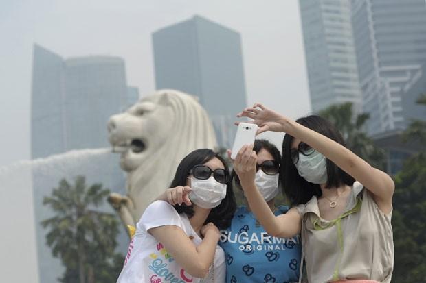 Moradores saem com máscaras em Cingapura (Foto: Joseph Nair/AP)