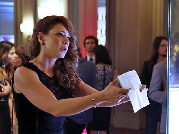 A loira fica desesperada e pega o convite para provar que foi chamada (Foto: Fábio Rocha / TV Globo)