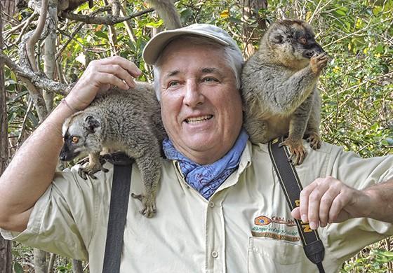O autor, que já esteve em Madagascar 16 vezes, é surpreendido pelo salto de dois lêmures-marrons em seus ombros (Foto: © Mitiko Magalhães)