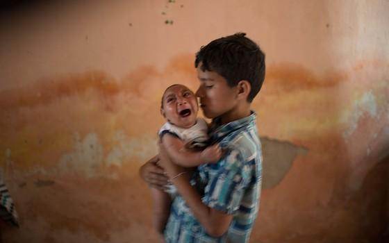 Garoto de 10 anos segura no colo irmão de dois meses que nasceu com microcefalia em Pernambuco (Foto: AP Photo/Felipe Dana, File)