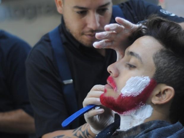 O cabeleireiro Rafael Roriz trabalha no rosto de um cliente que pediu uma barba vermelha (Foto: Divulgação/ Club Men Salon)
